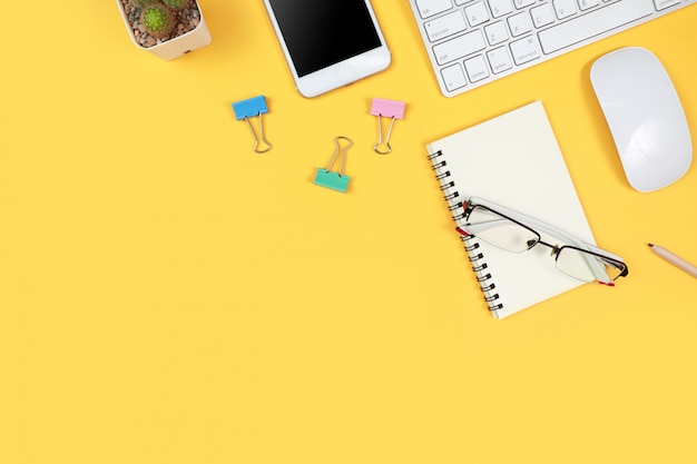 Arbeitsplatz mit laptop-computer und büroartikel auf gelb