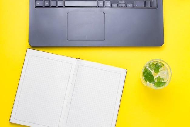 Arbeitsplatz mit laptop, ein frisches getränk mit eis und minze, ein offenes tagebuch auf einem gelben. konzept des arbeitsbereichs eines journalisten, schriftstellers, freiberuflers, texters. flache lage, draufsicht