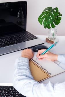 Arbeitsplatz mit laptop, jungenschülerhänden mit pfanne über notizbuch und grüner pflanze auf einem weißen tisch.