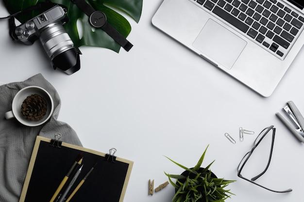 Arbeitsplatz mit laptop, kamera und gläsern, draufsicht mit kopienraum