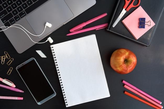 Arbeitsplatz mit laptop, notizblock, kopfhörern, apfel und smartphone draufsicht. von zuhause aus arbeiten.
