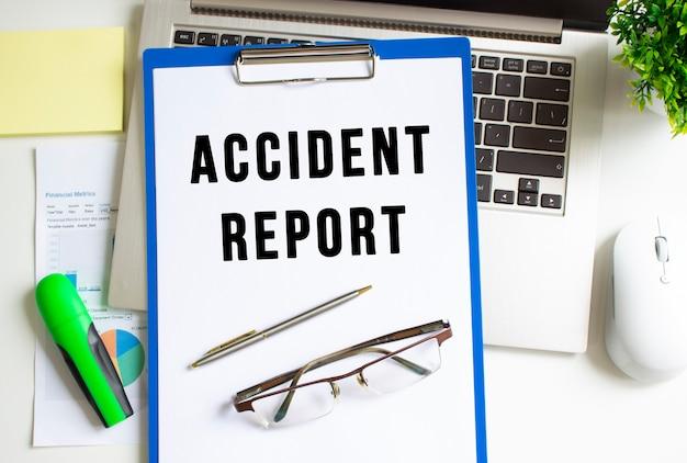 Arbeitsplatz mit laptop, ordner und diagramm auf dem tisch. der ordner mit dem text unfallbericht.