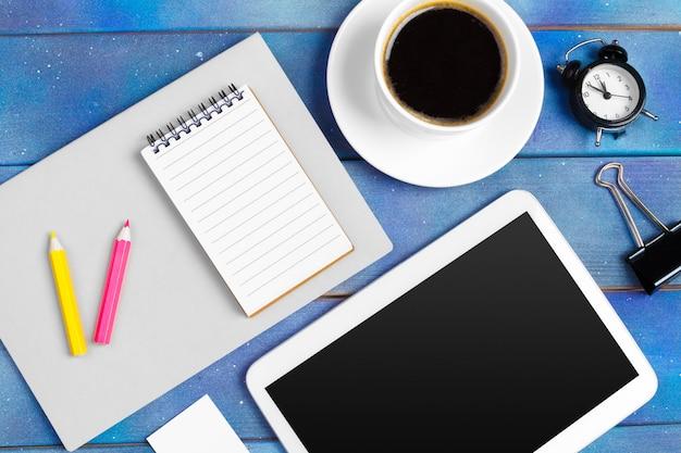 Arbeitsplatz mit leerer digitaler tablette, papier auf blauer hölzerner arbeitstabelle. oben aufgenommene ansicht