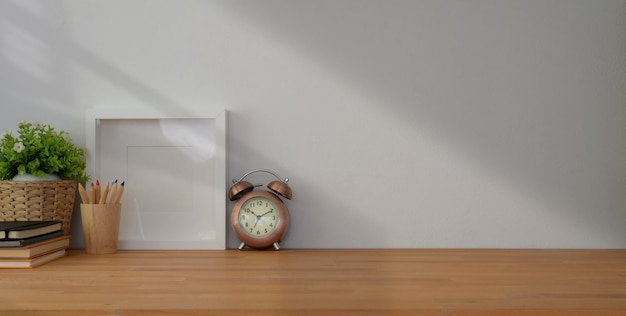 Arbeitsplatz mit mock-up-frame und büromaterial auf holztisch und weiße wand
