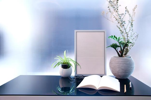 Arbeitsplatz mit modernem notizbuch auf glastisch, houseplant und zubehör.