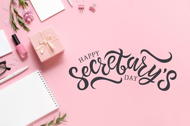 Arbeitsplatz mit notizblock, stift, geschenk und anderem zubehör auf rosa hintergrund. happy secretary day schriftzug