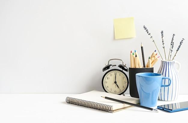 Arbeitsplatz mit notizblock, telefon, bleistiften, kaffee, uhr und leerem klebrigem papier auf weißem tisch über weißer wand. vorderansicht, mockup mit kopienraum