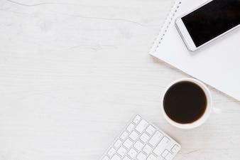 Arbeitsplatz mit Notizbuch Smartphone und Kaffee
