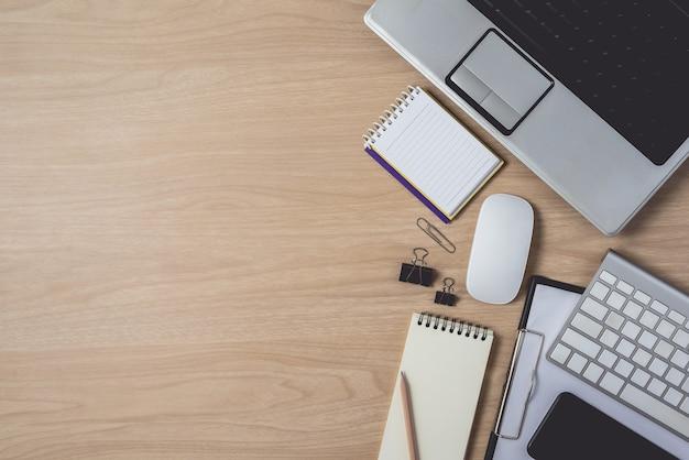 Arbeitsplatz mit notizbuch und laptop auf hölzernem hintergrund