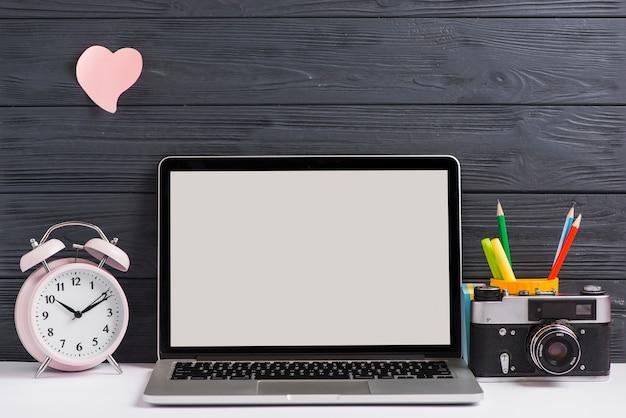 Arbeitsplatz mit offenem laptop auf modernem hölzernem schreibtisch mit kamera und wecker