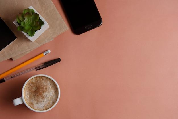 Arbeitsplatz mit smartphone, büroartikel und kaffeetasse auf korallenrotem hintergrund.