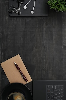 Arbeitsplatz mit smartphone, notebook, auf schwarzem tisch. draufsicht