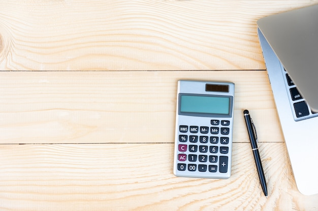 Arbeitsplatz mit taschenrechner, schwarzer stift, laptop auf dem kiefernholzhintergrund.