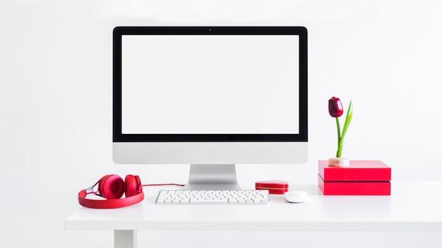 Arbeitsplatz mit tastatur in der nähe von monitor, computermaus, verzierungsblume und kopfhörern