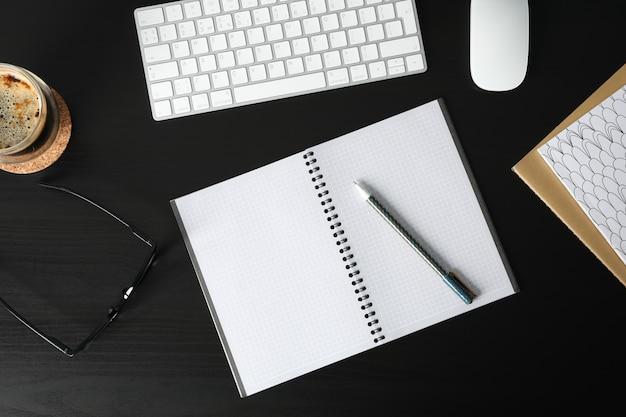 Arbeitsplatz mit tastatur, tasse kaffee und leerem notizbuch auf schwarzem holz, draufsicht