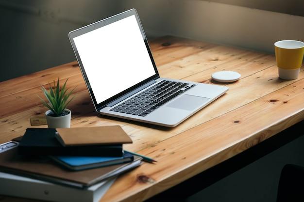Arbeitsplatz mit weißem leerem bildschirm des laptops im heimbüro
