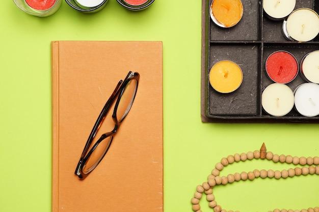 Arbeitsplatz oder schreibtisch mit braunen kerzen und einem buch. lesekonzept. flach legen flaches design