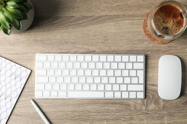 Arbeitsplatz. tastatur, maus, pflanze, tasse kaffee und notizbuch auf holz, draufsicht