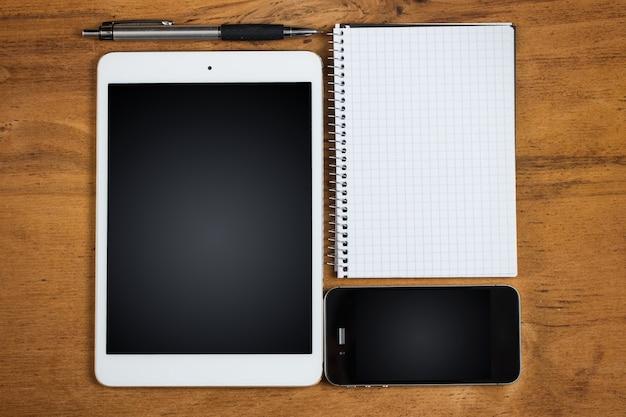 Arbeitsplatz. telefon, tablet und notizblock auf dem tisch