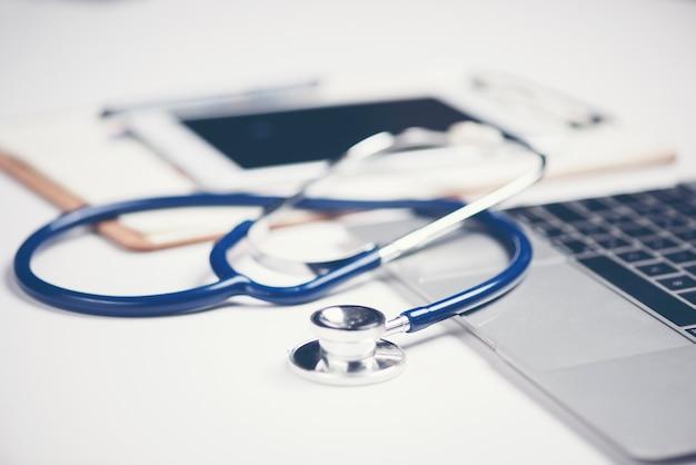 Arbeitsplatz von doktor mit laptop und stethoskop und notizbuch auf weißer tabelle