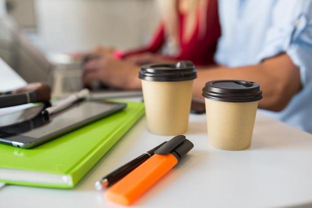 Arbeitsplatz von menschen, die zusammen im büro auf laptop arbeiten
