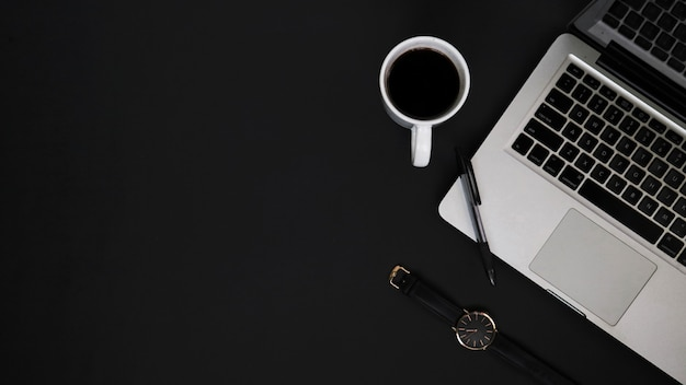Arbeitsplatz von oben mit laptop-stiftuhr und kaffeetasse