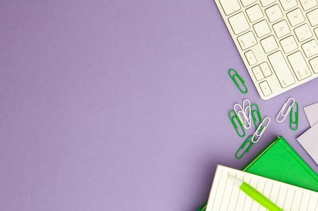 Arbeitsplatzanordnung auf purpurrotem hintergrund mit kopienraum