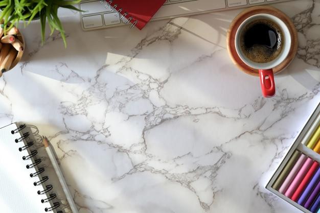 Arbeitsplatzcomputer auf marmortisch und kreatives designmaterial