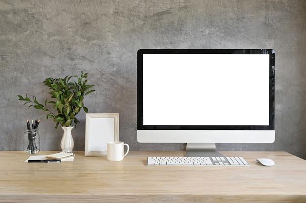 Arbeitsplatzcomputermodell und fotorahmen, kaffee mit betriebsdekoration auf hölzerner tabelle und dachbodenwand.