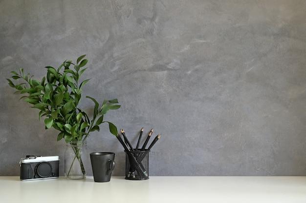 Arbeitsplatzkamera, kaffee, bleistift und anlage verzieren auf weißer schreibtisch- und dachbodenwand.