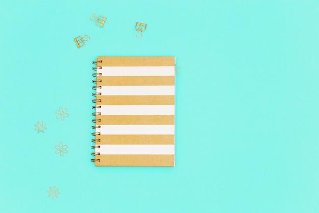 Arbeitsplatzkonzept für schule oder büro flache lage mit geschlossenem notizbuch auf goldener büroklammer des frühlings