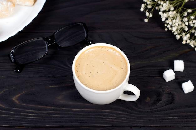 Arbeitsplatzmodell mit einer tasse cappuccino-kaffee auf einem dunklen holztisch.