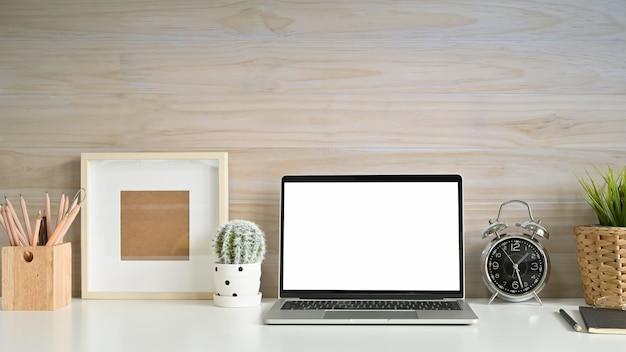 Arbeitsplatzmodelllaptop, fotorahmen, bleistift und kaktus auf schreibtisch mit hölzerner wand.