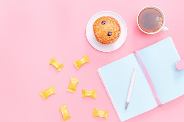 Arbeitsplatzschreibtisch-büroartikel, heißer tee, süßigkeit und kuchen auf rosa pastellhintergrund