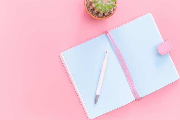 Arbeitsplatzschreibtisch-büroartikel mit kaktus auf rosa pastellhintergrund
