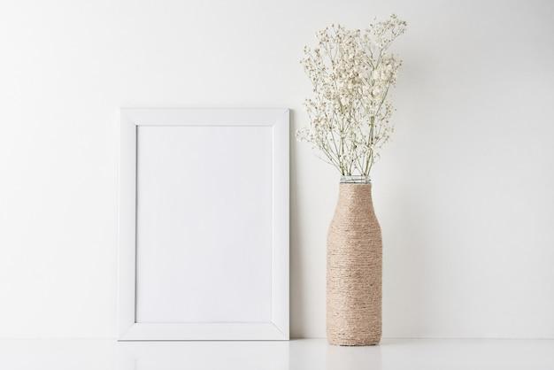 Arbeitsplatzschreibtisch mit leerem rahmen und blume im vase