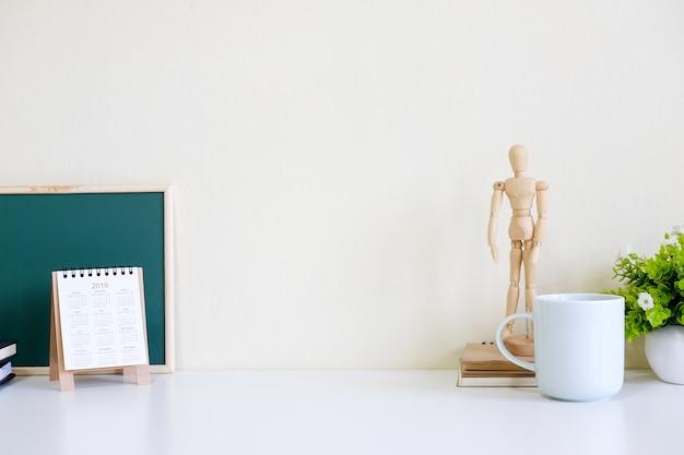 Arbeitsplatzspott oben mit hölzernem vorbildlichem spielzeug, tasse kaffee, kalender auf bürotisch.
