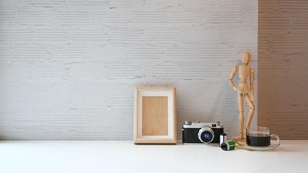 Arbeitsplatztabelle kamerafilm und filmstreifen, fotorahmen und kaffee auf weißer tabelle.