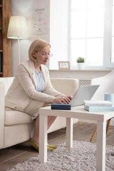 Arbeitsprozess. aufmerksame reife geschäftsfrau, die beim sitzen auf der couch tippt