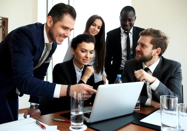 Arbeitsprozess des geschäftsteams. professionelle fotocrew, die mit neuem startup-projekt arbeitet. treffen der projektleiter. analysieren sie geschäftspläne laptop.