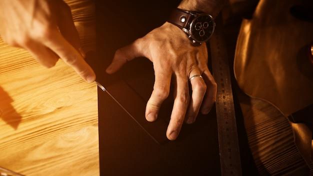 Arbeitsprozess des ledergürtels in der lederwerkstatt. mann, der werkzeug hält. gerber in alter gerberei. holztischoberfläche. nahaufnahme mann arm. warmes licht für text und design. web-banner-größe