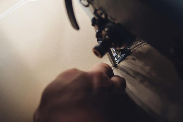 Arbeitsprozess des lederhandwerkers. gerber näht leder auf einer speziellen nähmaschine, nahaufnahme. arbeiter näht lederprodukt an der nähmaschine. werkstatt für lederhandwerker.