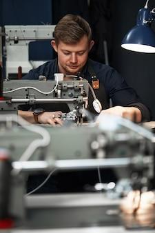 Arbeitsprozess des lederhandwerkers. gerber oder skinner näht leder auf einer speziellen nähmaschine, nahaufnahme. arbeiter näht an der nähmaschine.
