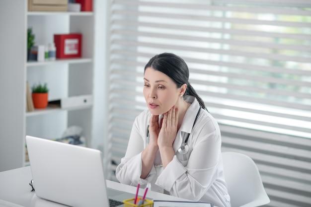 Arbeitsprozess. erfolgreiche hübsche frau in einem weißen gewand sitzt vor einem laptop und schaut sorgfältig auf den bildschirm in ihrem büro.