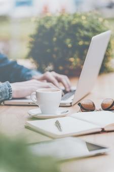 Arbeitsprozess. nahaufnahme eines jungen mannes, der am laptop arbeitet, während er im straßencafé sitzt