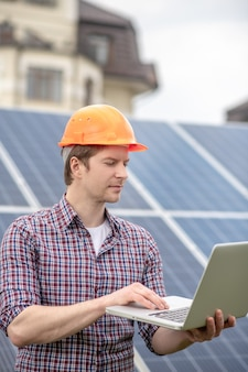 Arbeitsprozess. profil eines interessierten ernsthaften mannes mit schutzhelm, der aufmerksam auf den laptop schaut, der in der nähe des solarpanels steht