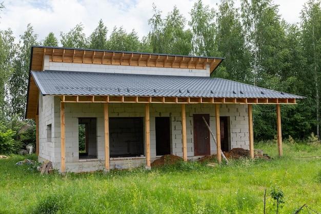 Arbeitsprozess, vorortbau aus silikat- und gassilikatblöcken und holz. der rahmen eines einstöckigen hauses mit dach.