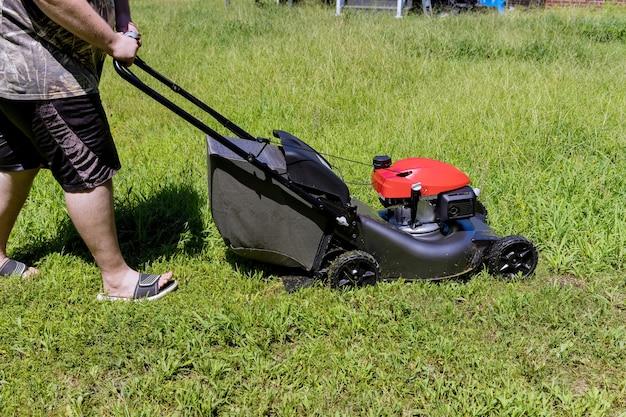 Arbeitsrasenmäher auf grünem rasen mit getrimmtem gras im gartenpflegewerkzeug