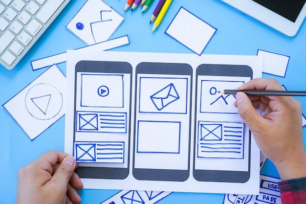 Arbeitsschreibtisch mit hände skizzieren von bildschirmen für die entwicklung von mobilen responsiven websites mit ui / ux