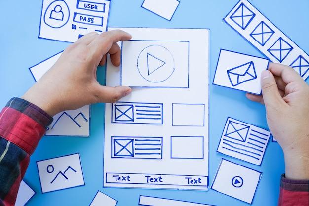 Arbeitsschreibtisch mit händen, die wireframe-bildschirme der mobilen responsive website sortieren.